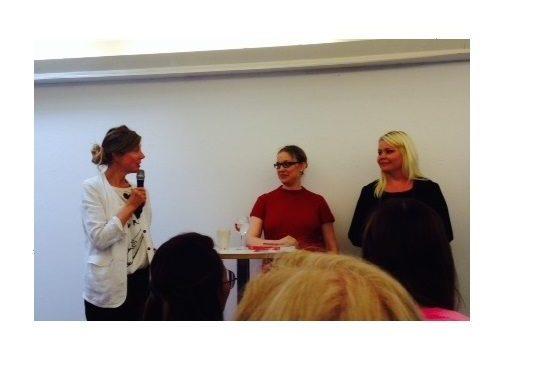Hanna-Karin i rött (fortfarande beklämmande gravid) och Eleonor i svart står vid ett bord och svarar på frågor.