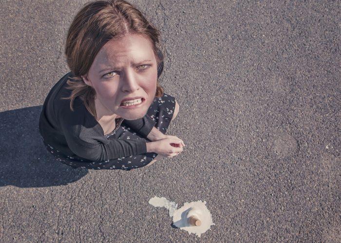 En kvinna sitter på huk. Bredvid henne på asfalten ligger en tappad glass.