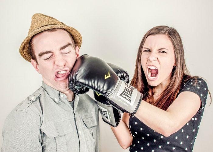 En kvinna med boxhandskar som slår en man i ansiktet.