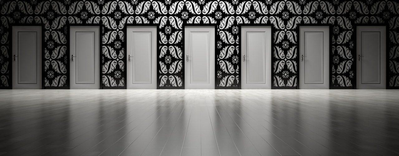 Många vita dörrar mot en svartvit-mönstrad tapet.