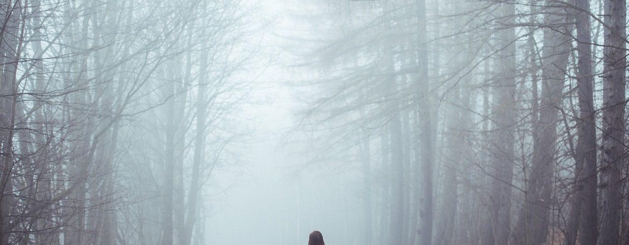 Kvinna som står med ryggen mot kameran och tittar längs vägen och in i dimman som ligger tung.