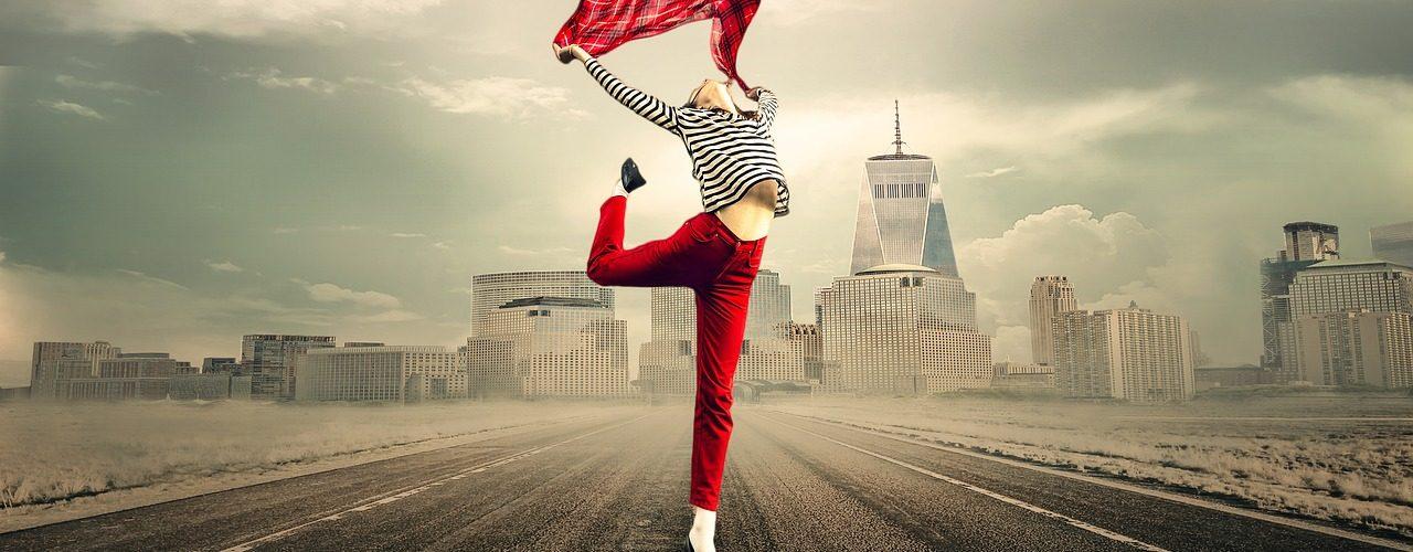 Kvinna med röda byxor och svartvit tröja dansar med en röd scarf över huvudet