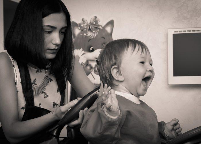 Mörkhårig frisör klipper koncentrerat ett litet barns hår. Barnet skriker - eller skrattar.