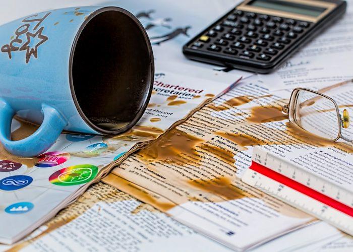 En vält kaffekopp med kaffe över alla viktiga papper