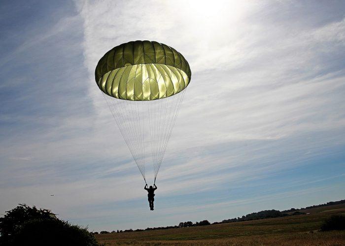 Fallskärmshoppare med grön fallskärm landar säkert på marken.