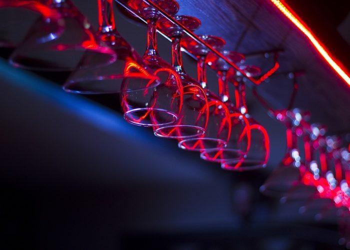 Vinglas hänger på rad i en bar.