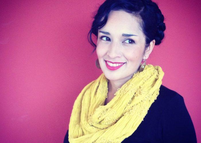 Kvinna med mörkt hår och stor gul sjal mot cerise bakgrund