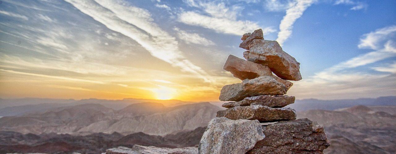 Ett tiotal stenar balanserar på varandra. Solnedgång över bergen i bakgrunden.