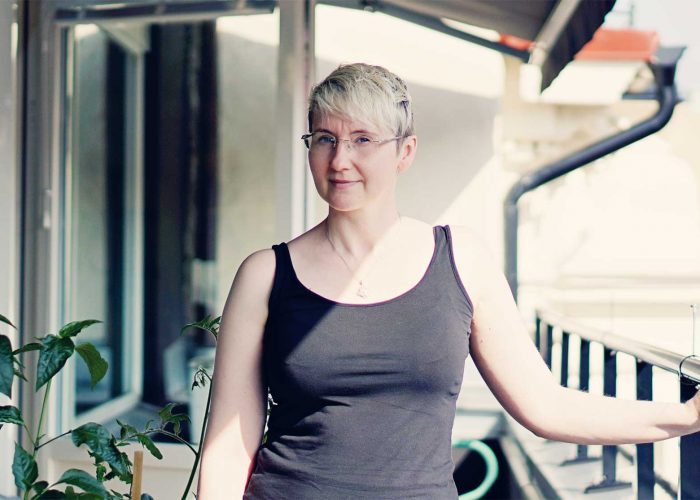 Therése Mellby, korhårig och med glasögon, står i linne på solig balkong.