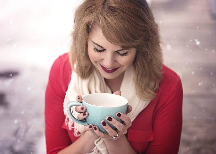 Kvinna med röda läppar coh röd tröja som lyckligt håller i en turkos kaffekopp.