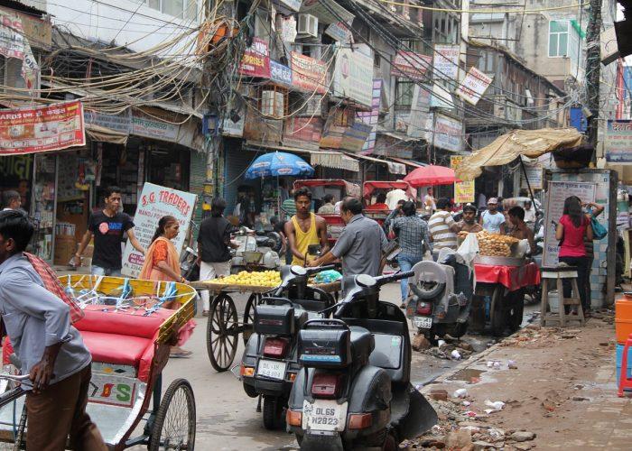 Bild från New Dehli med många bilar, stånd och elledningar som hänger från husen. Kaotiskt.