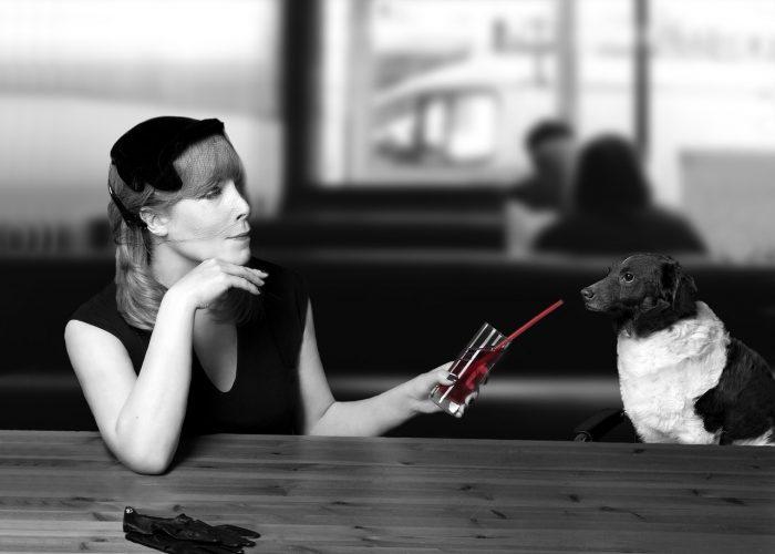 En svartklädd kvinna sitter i en bar. Hon sträcker sin drink mot en hund. Drinken har ett sugrör och är röd.