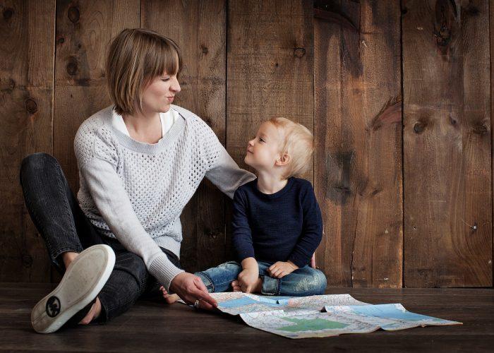 En mamma och hennes son sitter på golvet i en träbyggnad. De tittar på varandra. På golvet framför dem ligger en karta.