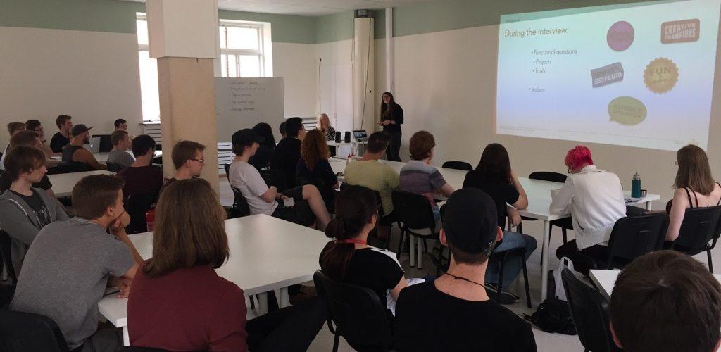 Ett klassrum där en stor grupp studenter sitter och lyssnar till en talare.