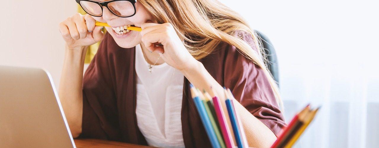 Flicka med långt hår och glasögon som sitter framför en bärbar dator och har en penna i munnen.