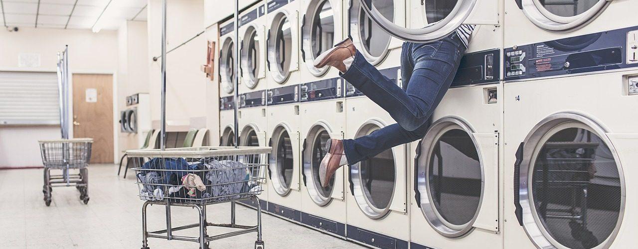 Två rader med tvättmaskiner. Hur den övre raden är ena lyckan öppen och ett par ben sticker ut.