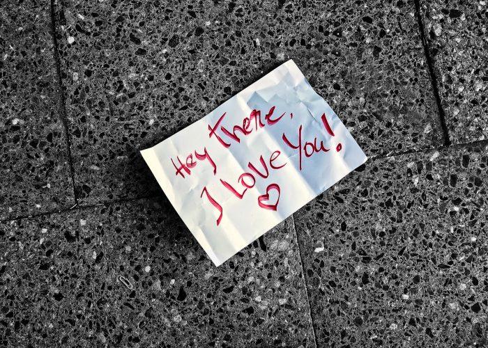 Ett papper som ligger på grå plattor. Texten är skriven i rött och lyder: Hey there I love you!