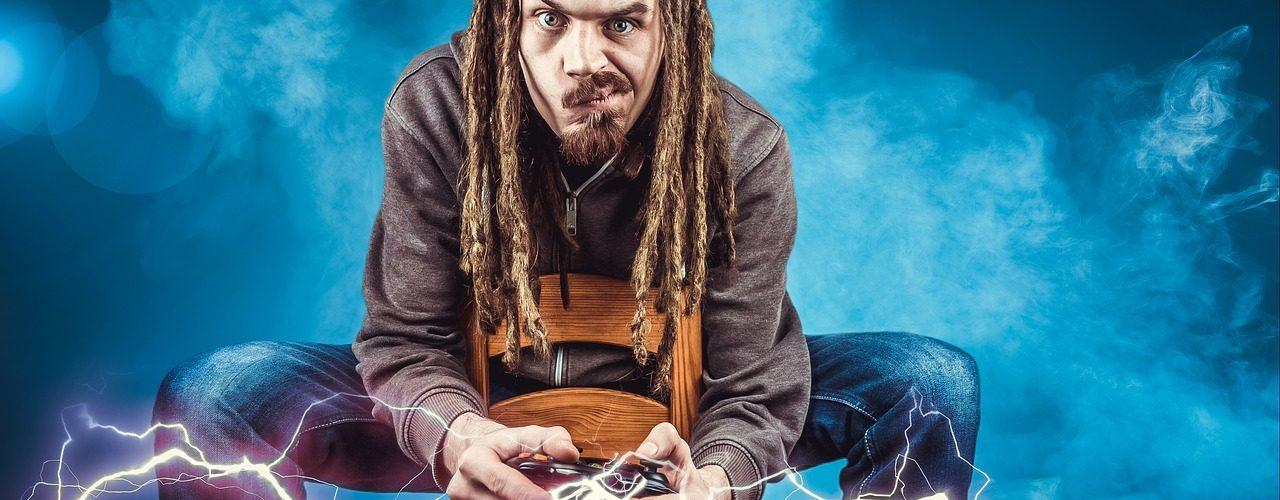 En man med dreadlocks sitter och spelar spel med djup koncentration.