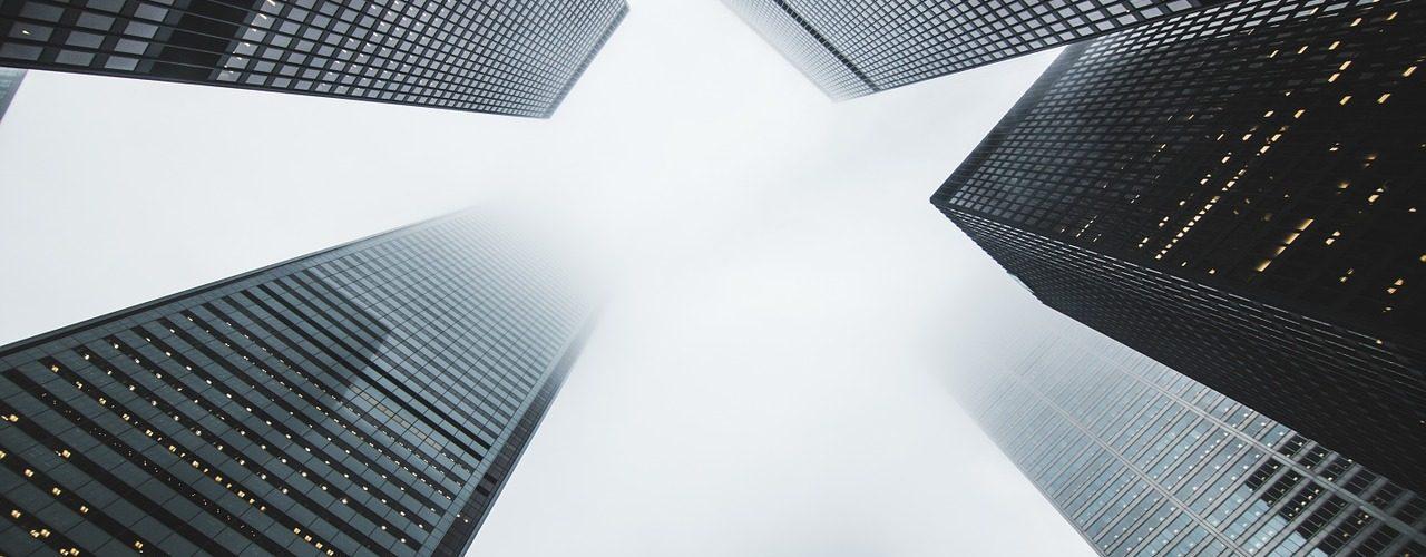 Perspektiv nedifrån upp mot himlen och höga skyskrapor.