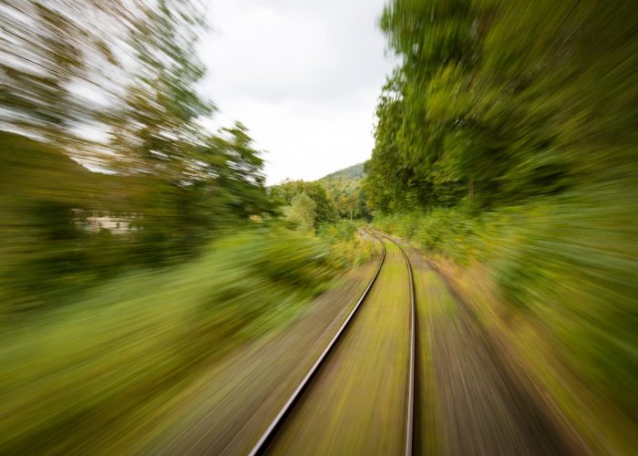 Tågspår mellan suddigt grönområde.