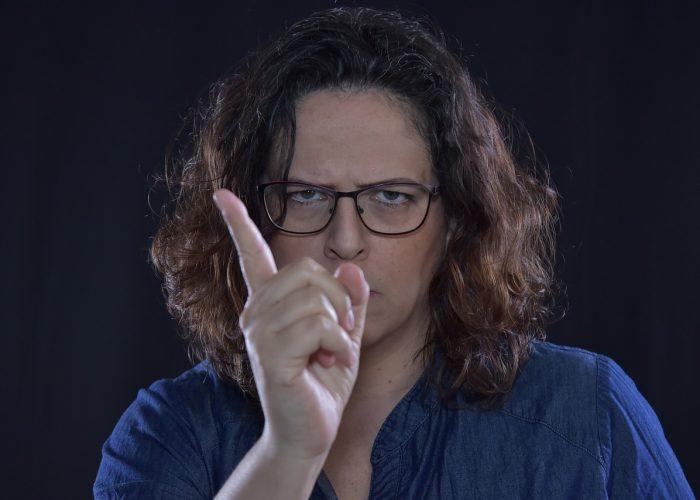 Argsint kvinna med permanentat brunt hår. Hon rynkar ögonbrynen och hytter med fingret.