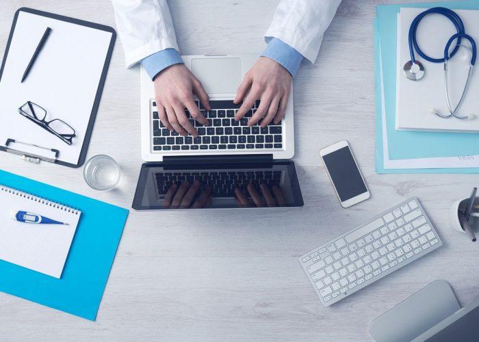 Läkare som sitter vid sin dator. Stetoskop och andra verktyg ligger runt honom.